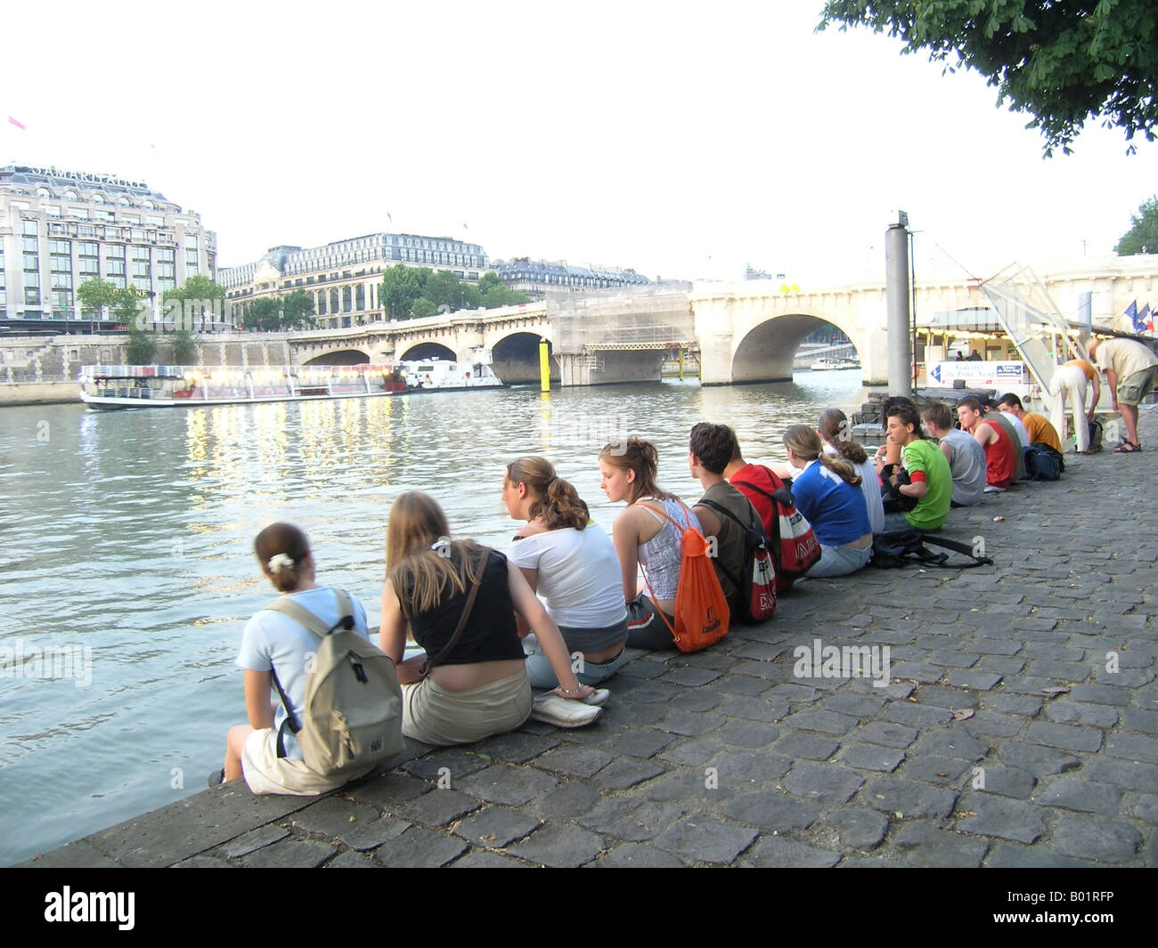 School group waiting on Seine river bank near Pont Neuf before a sightseeing boat trip - Stock Image