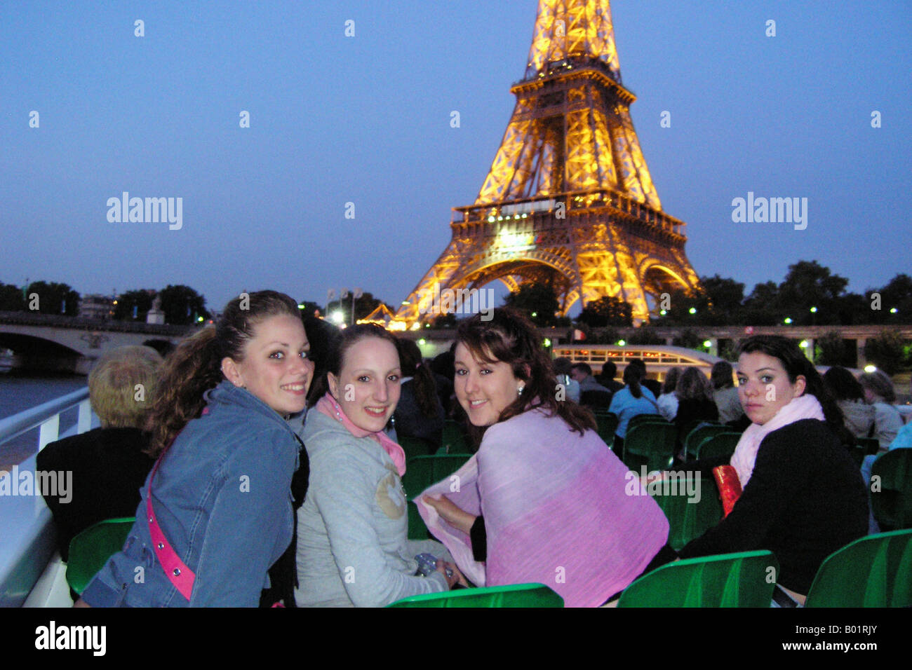 Teenagers on an evening boat trip across river Seine with Eiffel Tower in background Paris France - Stock Image