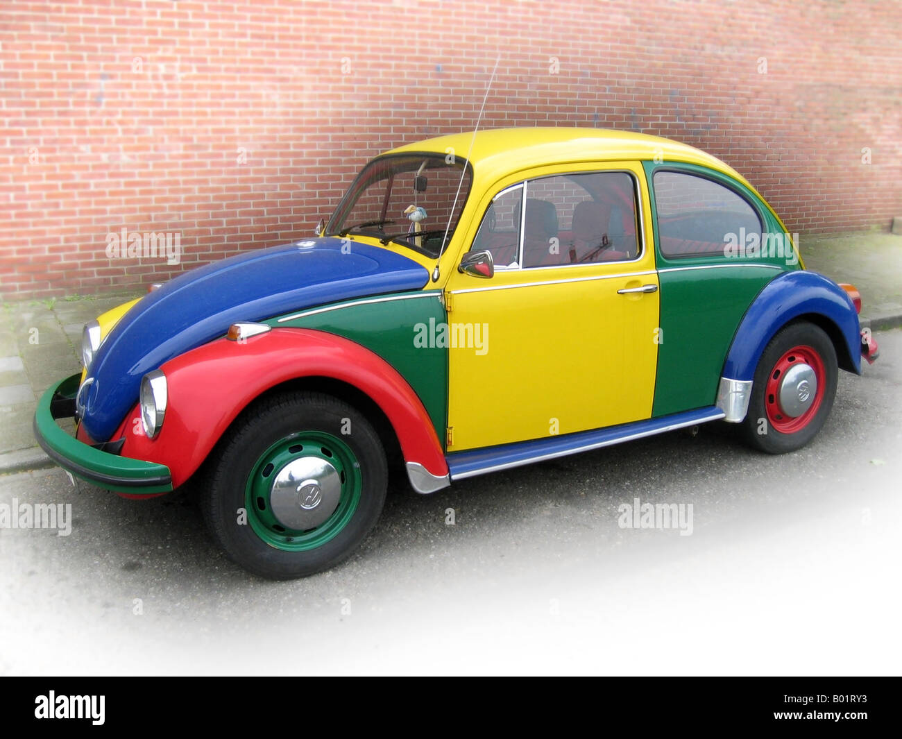 multi coloured VW beetle Harlequin - Stock Image