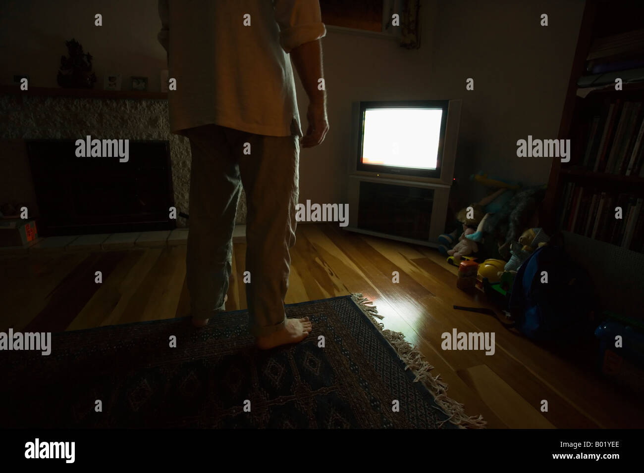 Man barefoot stands in front of television - Stock Image