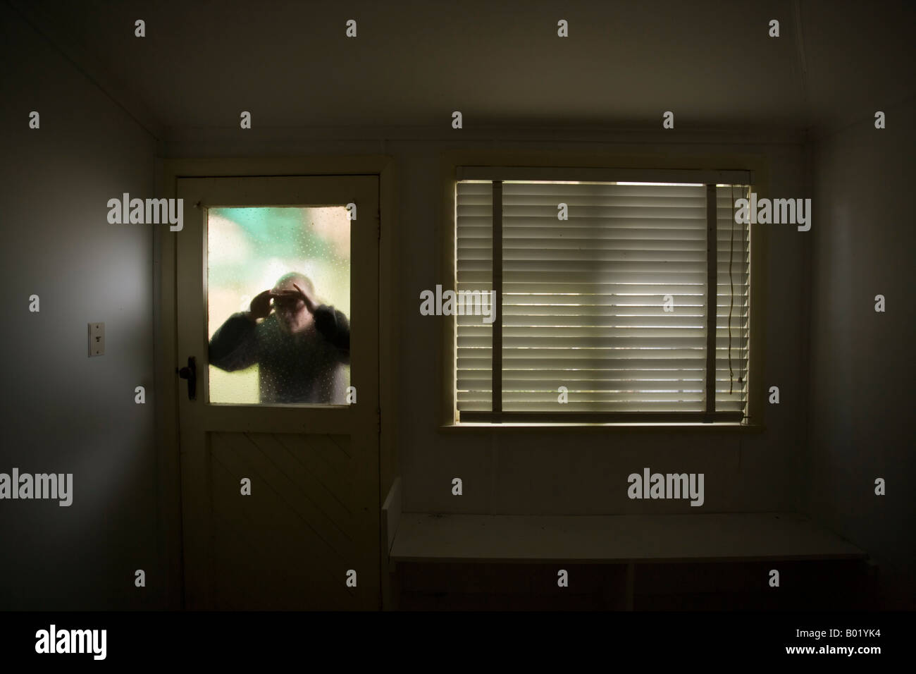 Man looks into room through frosted glass window pane on door beside window with blind - Stock Image