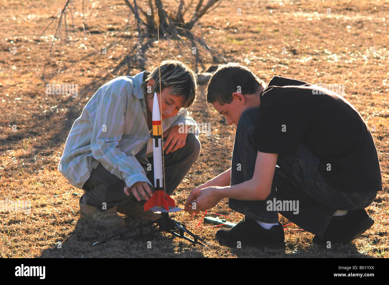 Two boys working together to fix the problem at hand - Stock Image