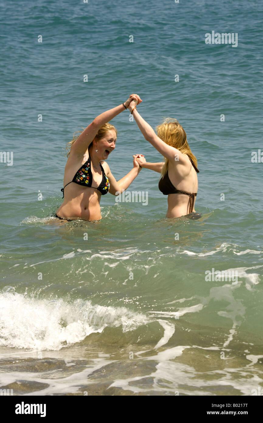 7e983613da8c67 Two young women frolicking in the Mediterranean Sea, Fuengirola beach, Costa  del Sol, Spain