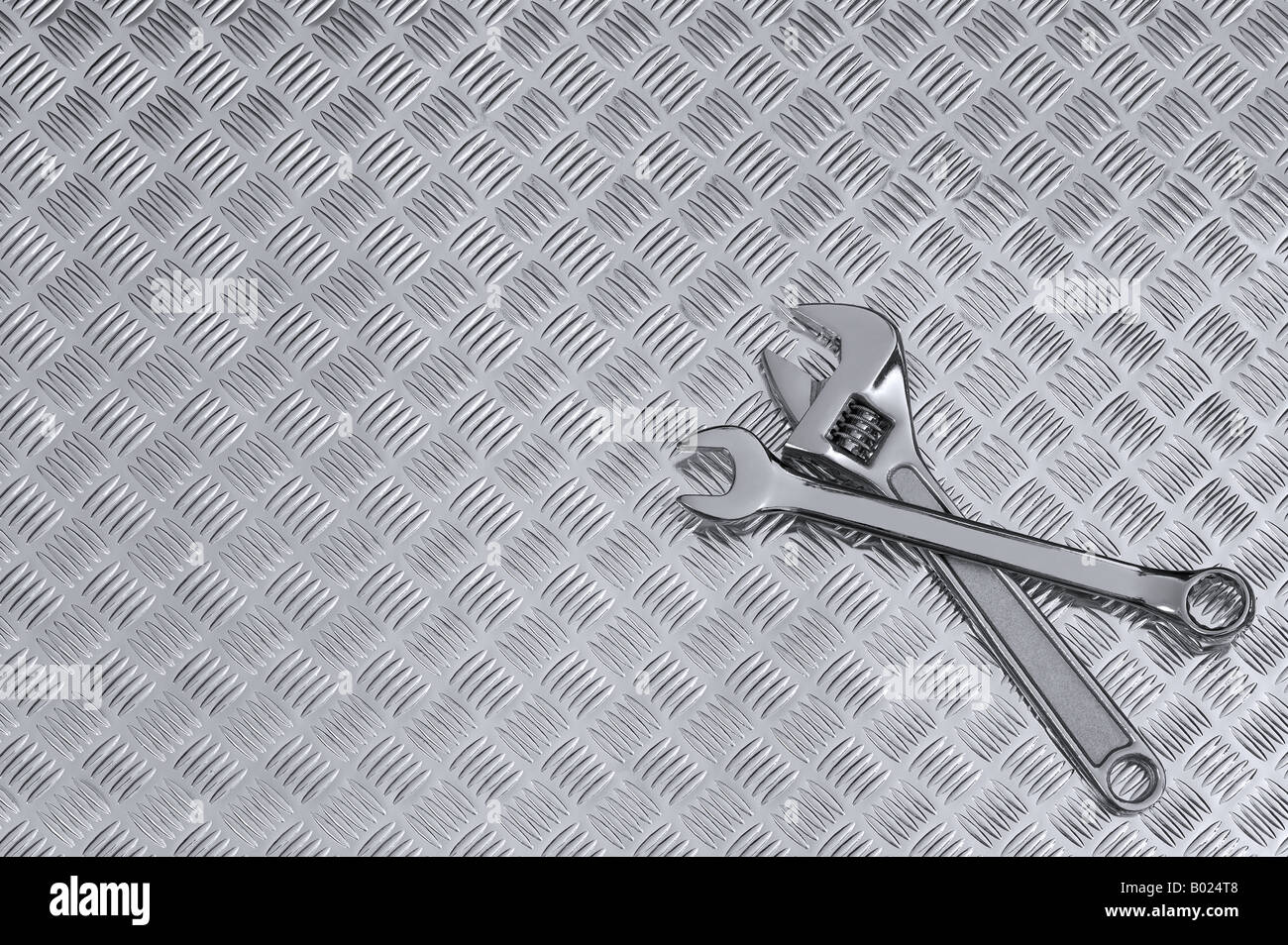 Mechanical background image of two spanners on a checkerplate workbench - Stock Image
