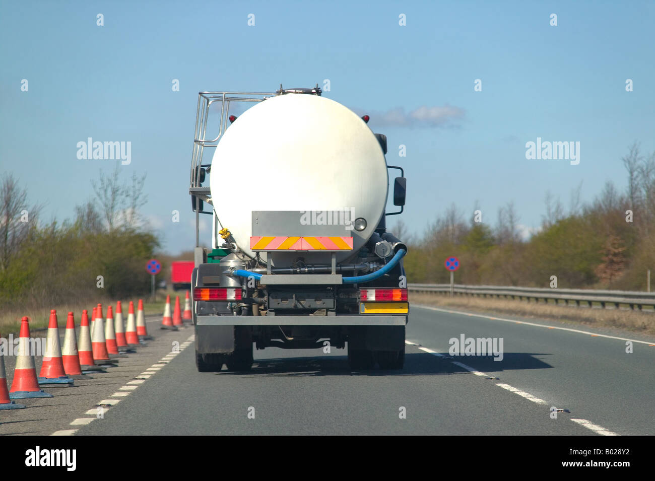 Rear view of a fuel tanker driving along a dual carriageway - Stock Image