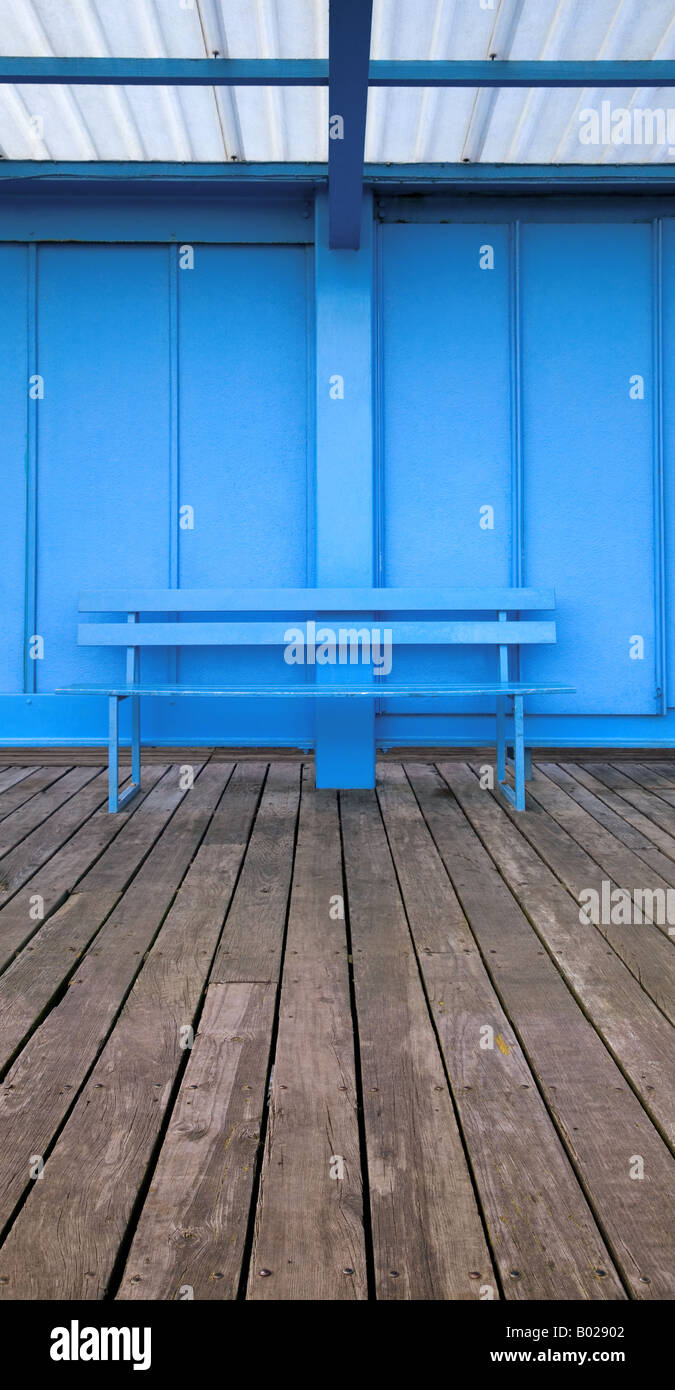 Vertical panoramic image of an empty blue bench on wooden decking - Stock Image