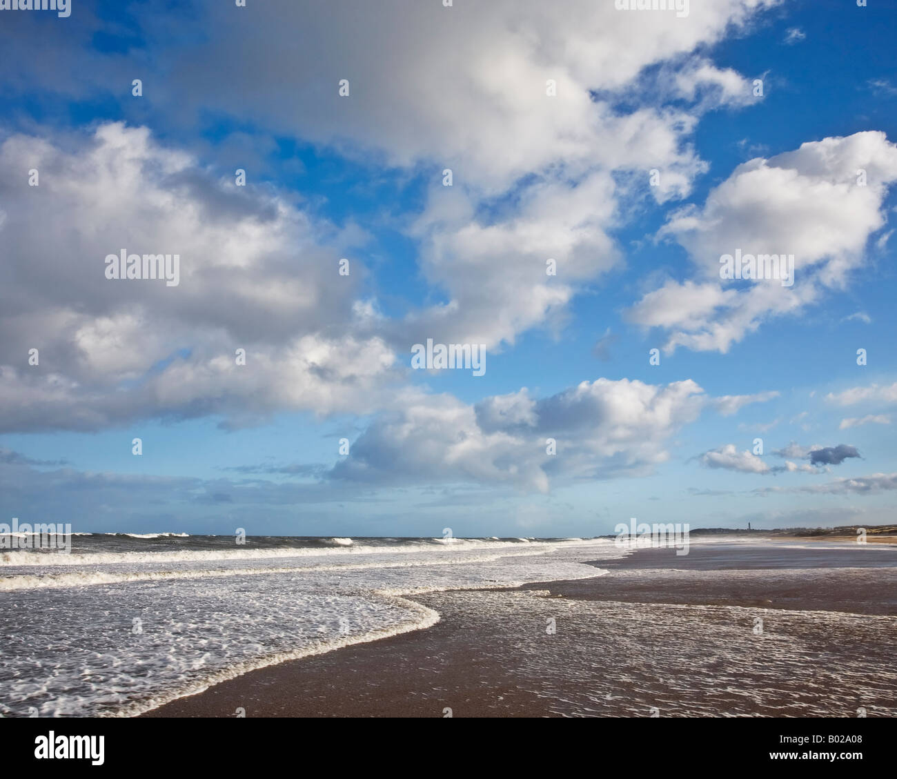 Clouds in a blue sky over the incoming tide on Druridge Bay on the Northumbrian coast, Northumberland, England - Stock Image