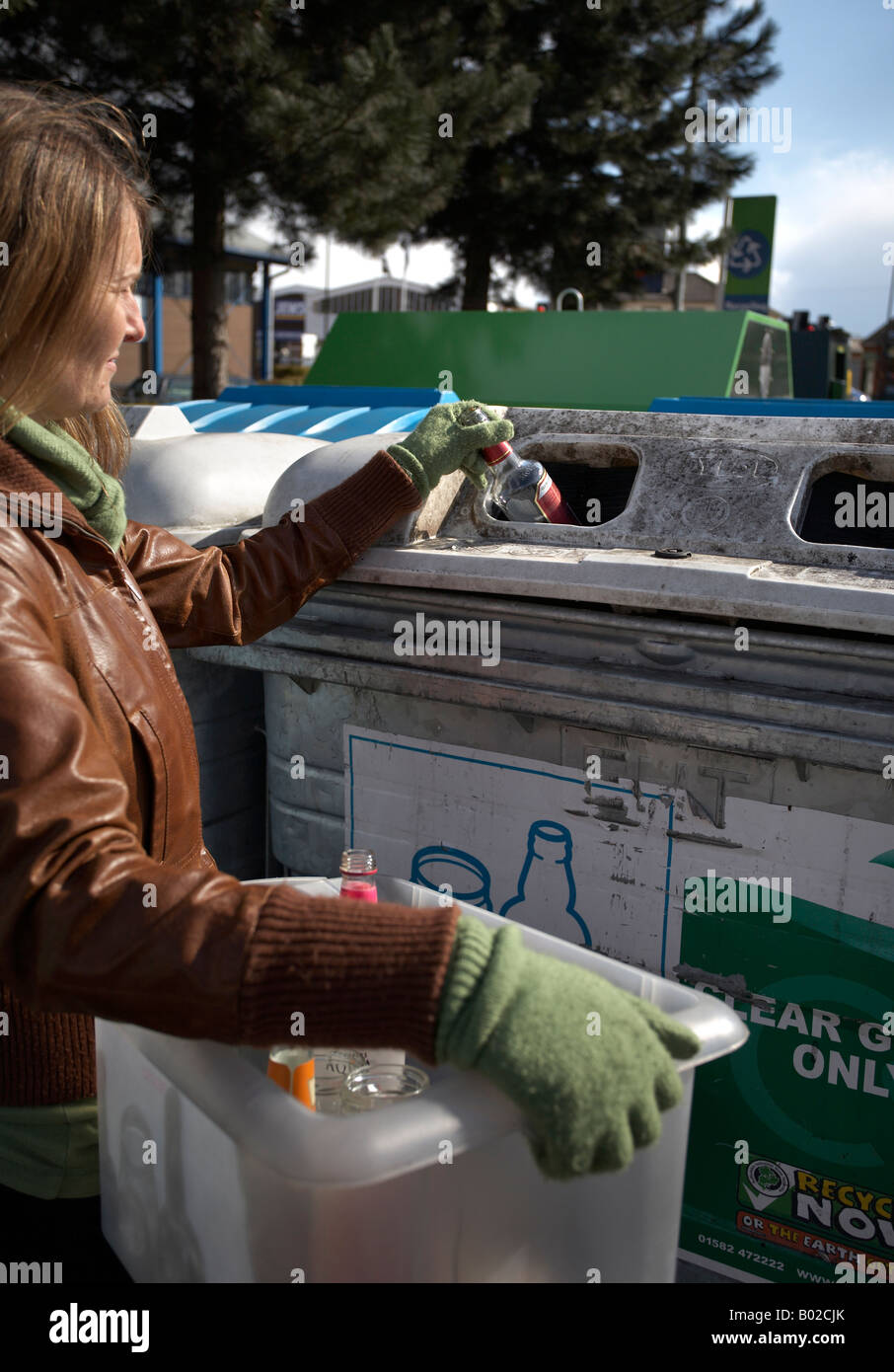 Woman recycling glass at a bottle bank - Stock Image