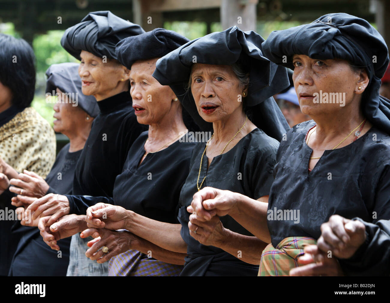 Indonesia Sulawesi Tana Toraja: traditional funeral. Family members, relatives and friends mourning in black clothes - Stock Image
