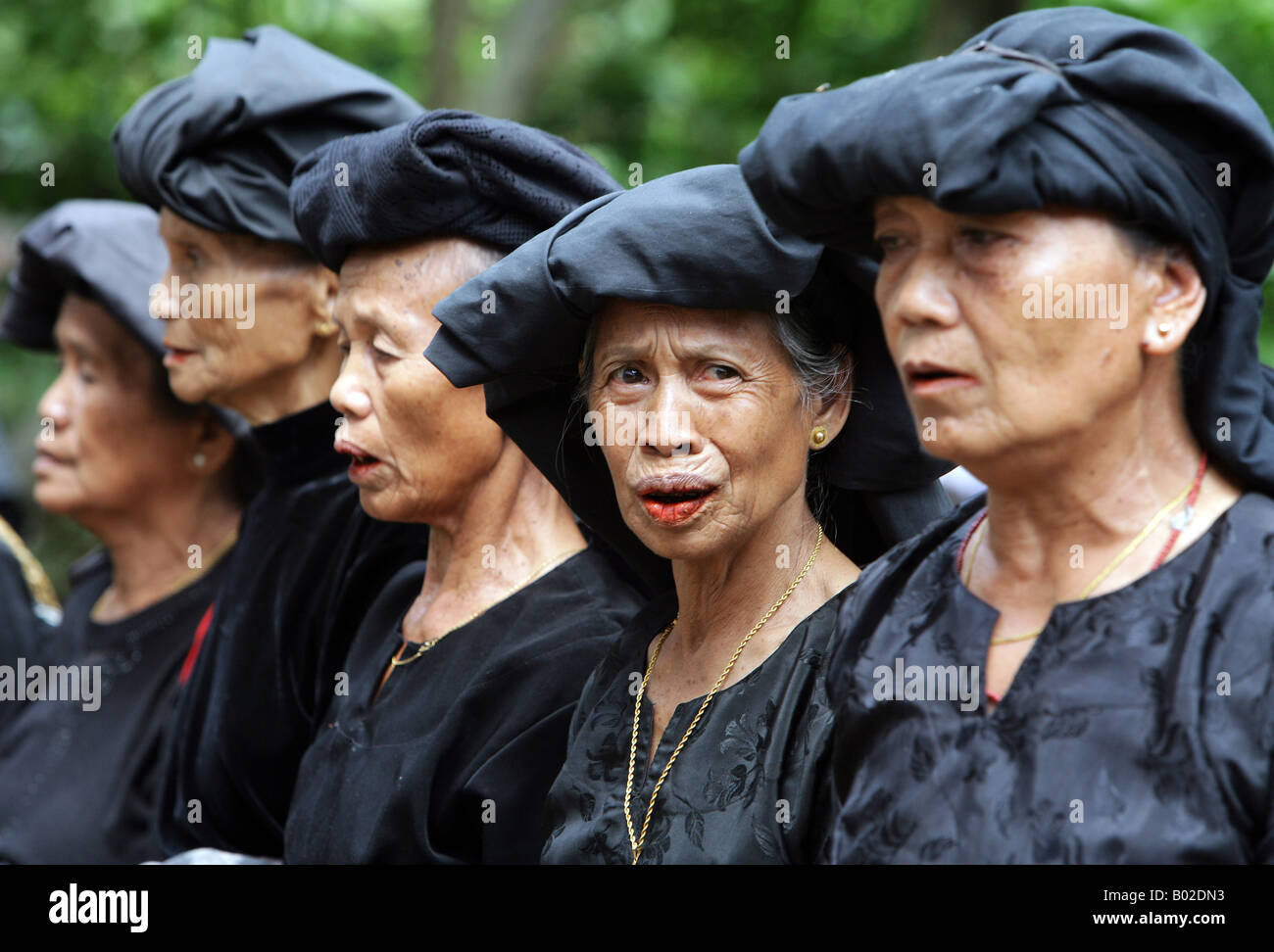 Indonesia Sulawesi Tana Toraja: traditional funeral. Family members, relatives and friends mourning in black clothes Stock Photo