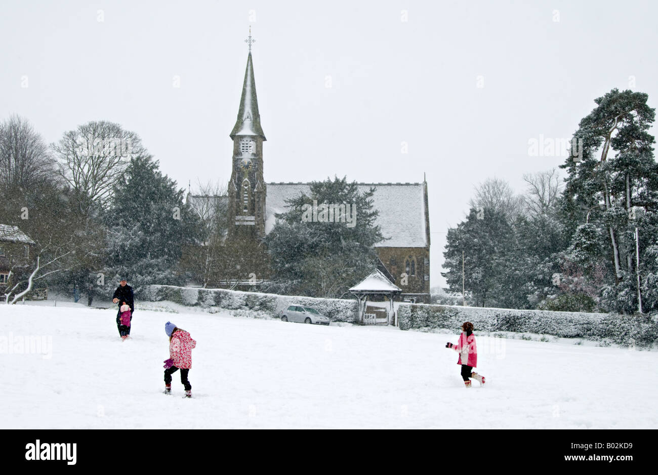 Ide Hill Village green in the snow.with children playing and St Mary's Church in the background - Stock Image