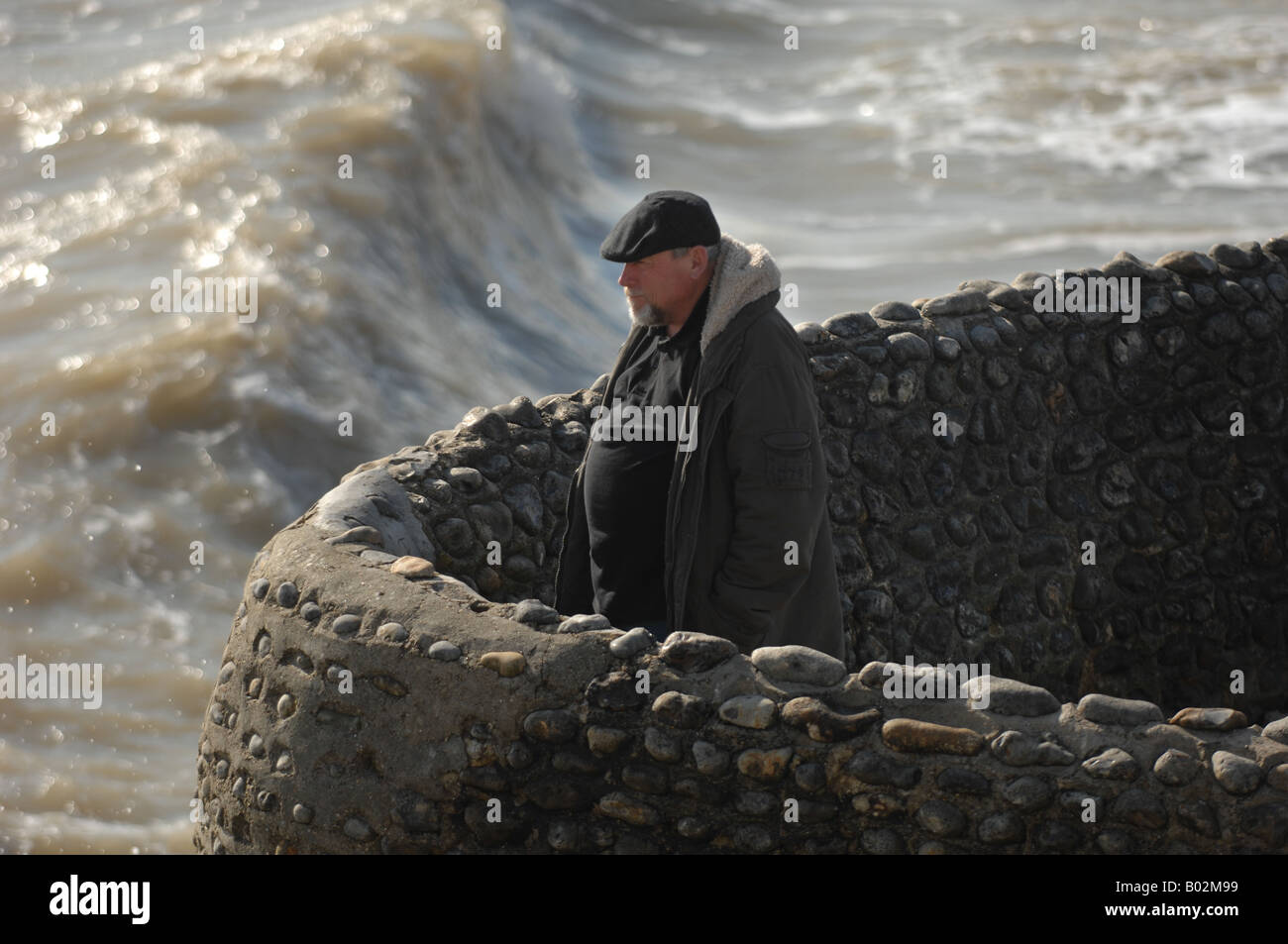 A man alone watches the sea in Brighton UK - Stock Image