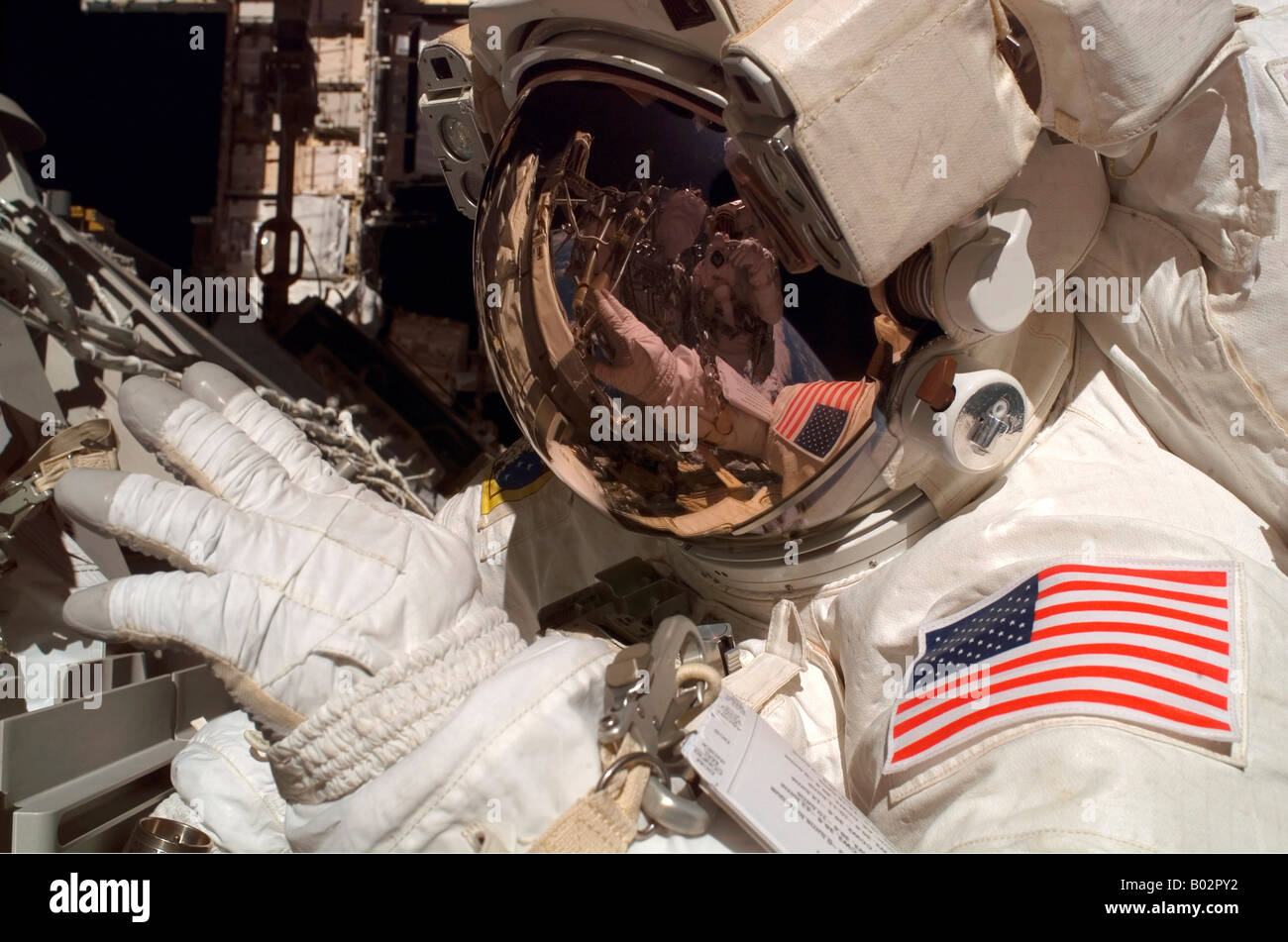 Close-up view of the helmet visor and spacesuit of an astronaut during a spacewalk. - Stock Image