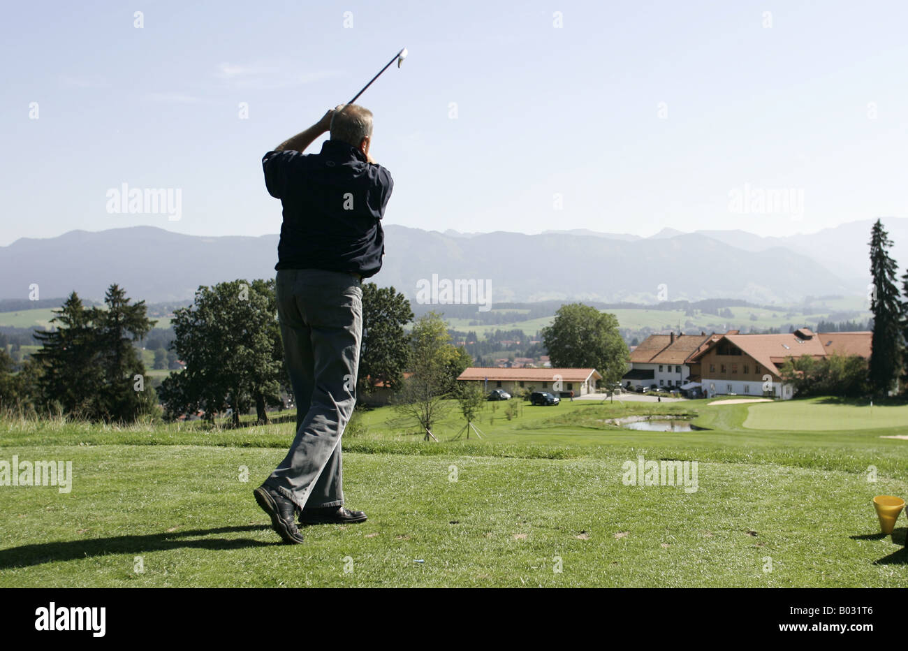 Golfer teeing off approaching hole 18 near the clubhouse. - Stock Image