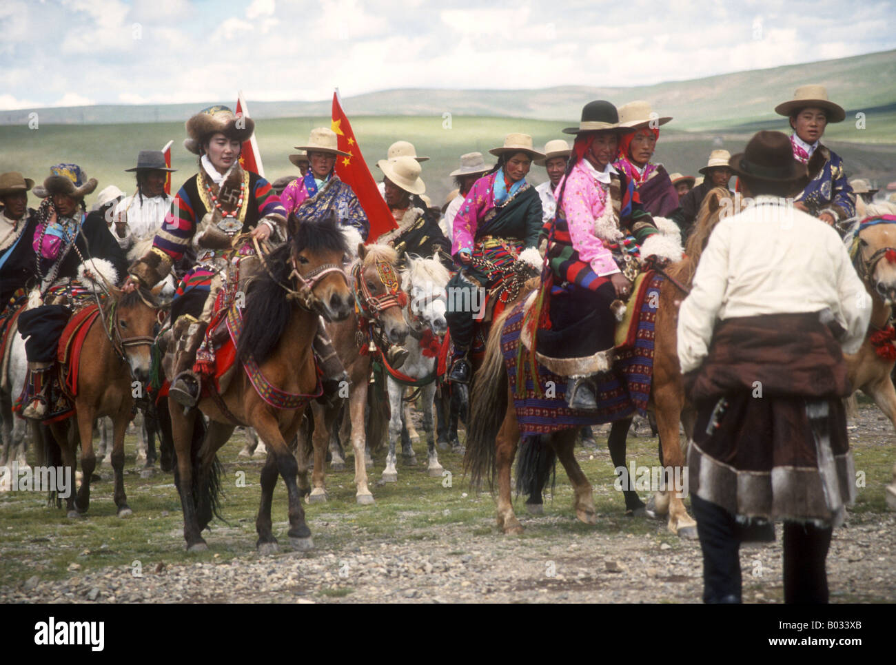 Horse riding display by traditionally dressed Tibetan girls at the annual Naqu Horse Fair in Northern Tibet - Stock Image