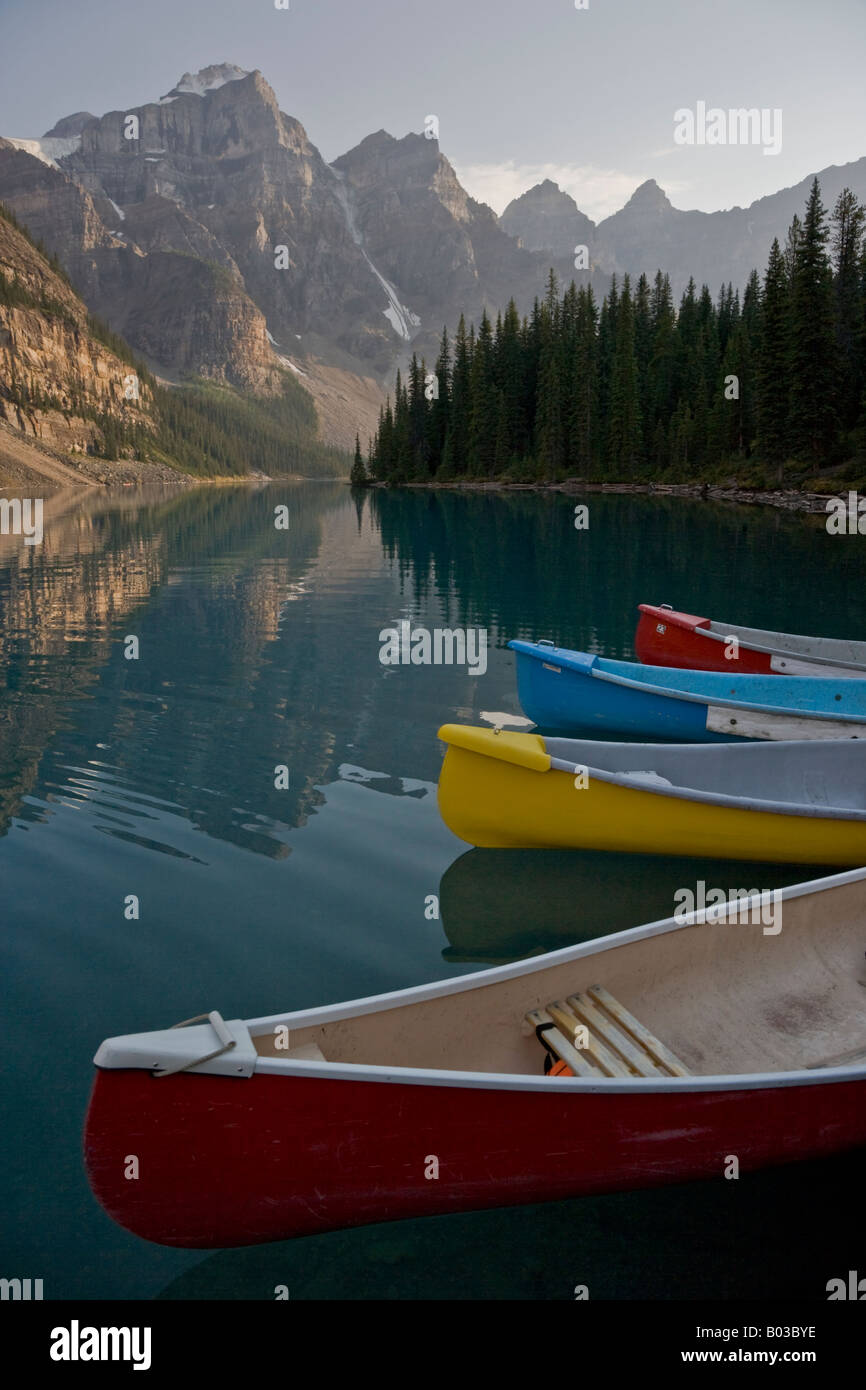 The sun setting on boats in Moraine Lake and the Valley of the Ten Peaks in Banff National Park, Alberta, Canada - Stock Image