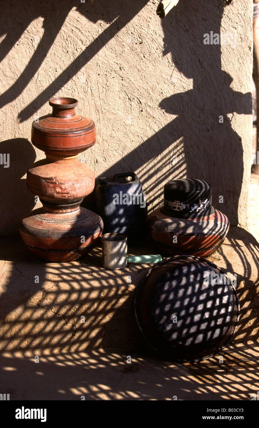 India Rann of Kutch Gujerat Banni area Harijan untouchable village water pots in dappled shade - Stock Image