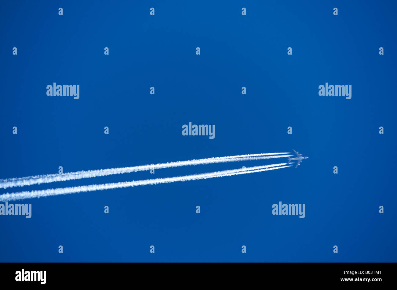 Plane in a blue sky. - Stock Image