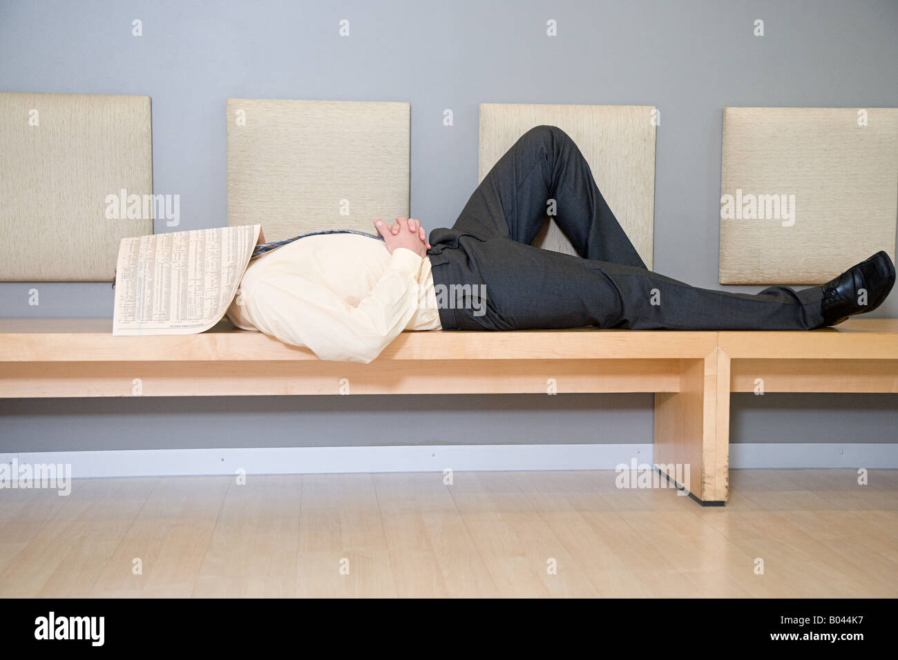 Man sleeping with newspaper over head - Stock Image