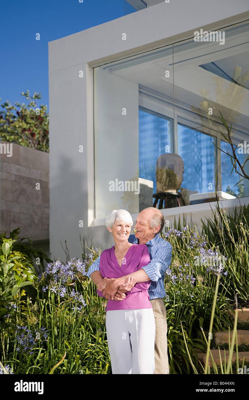 A senior couple stood in their garden - Stock Image