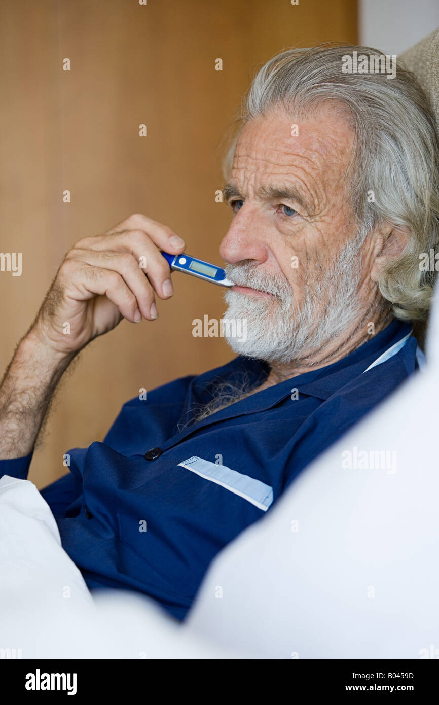Man using thermometer - Stock Image