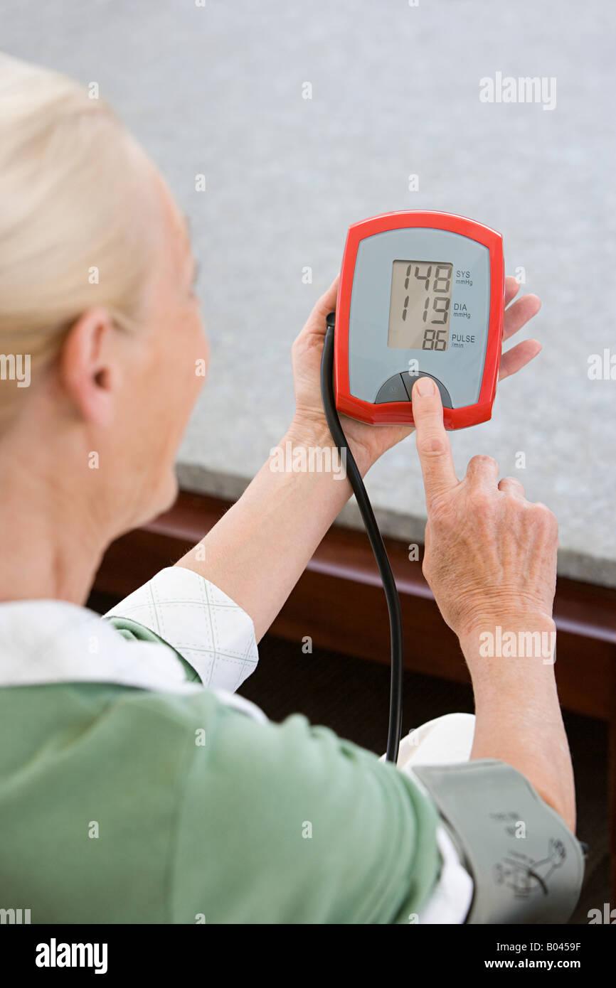 Woman using blood pressure gauge - Stock Image