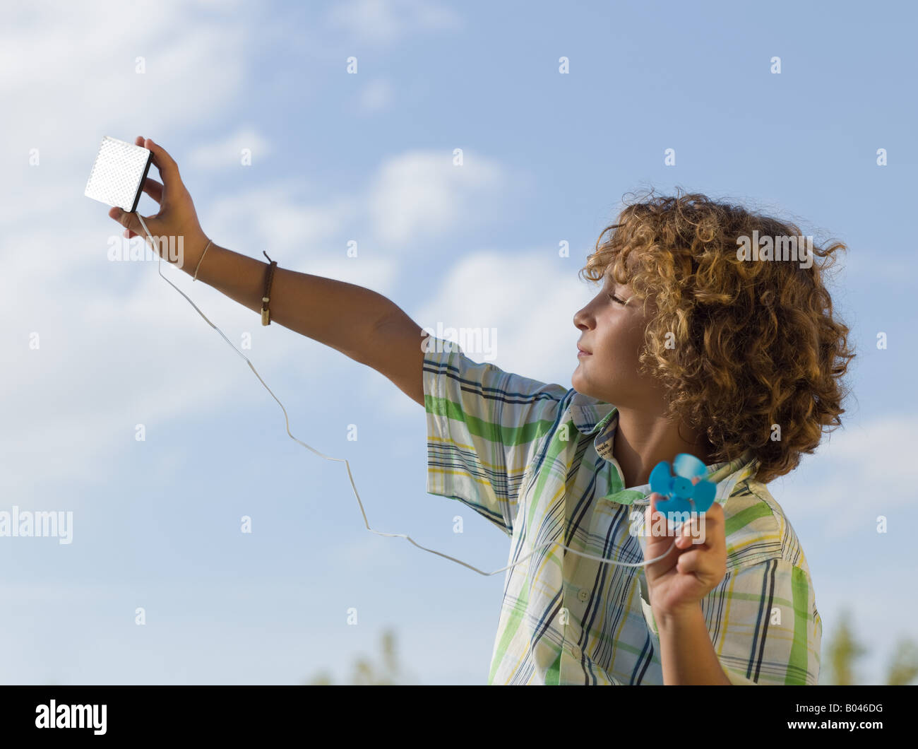 Boy using a small solar panel - Stock Image