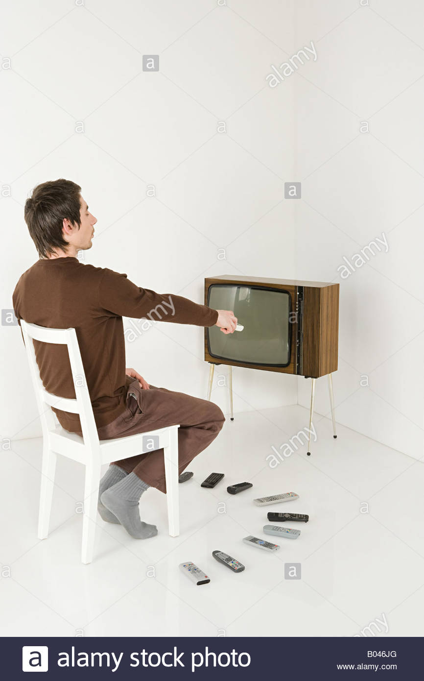 Man with television and remote controls - Stock Image