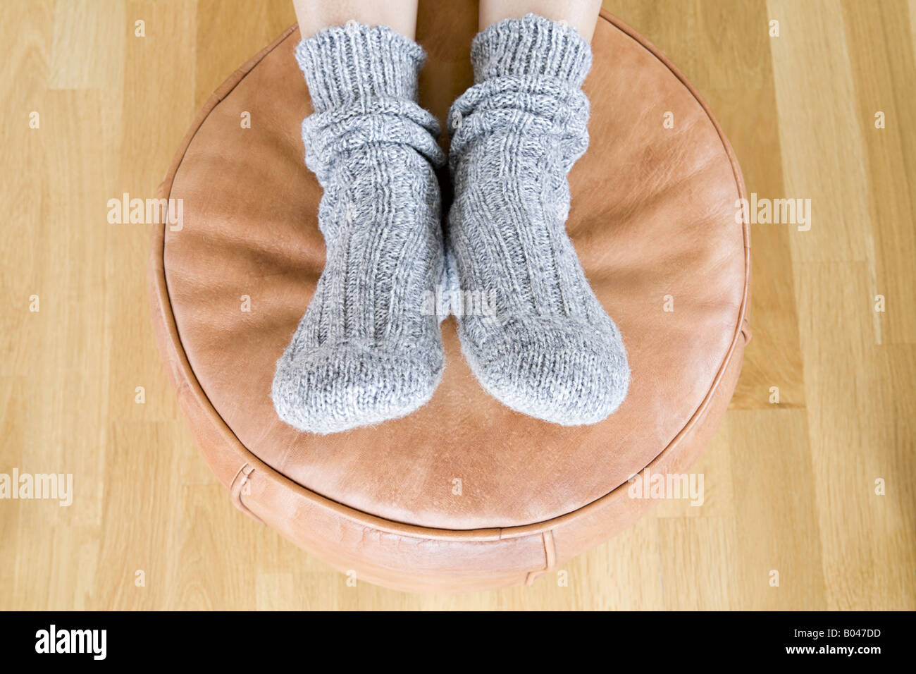 Person with feet on foot stool - Stock Image