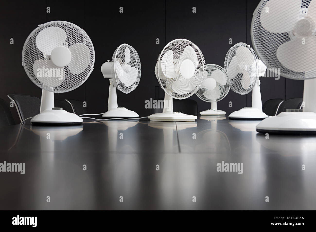 Electric fans on a conference table - Stock Image