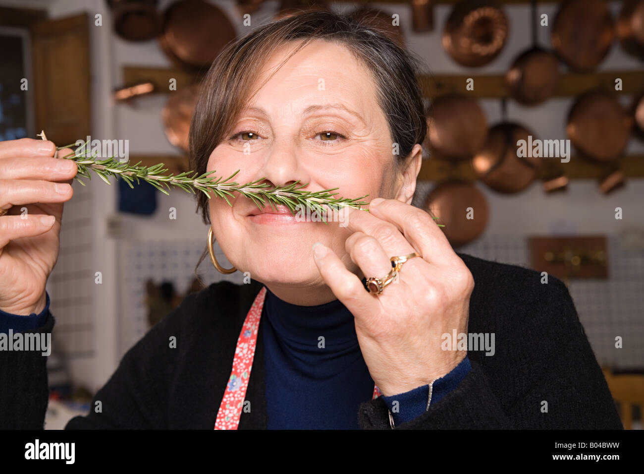 Woman smelling a sprig of rosemary - Stock Image