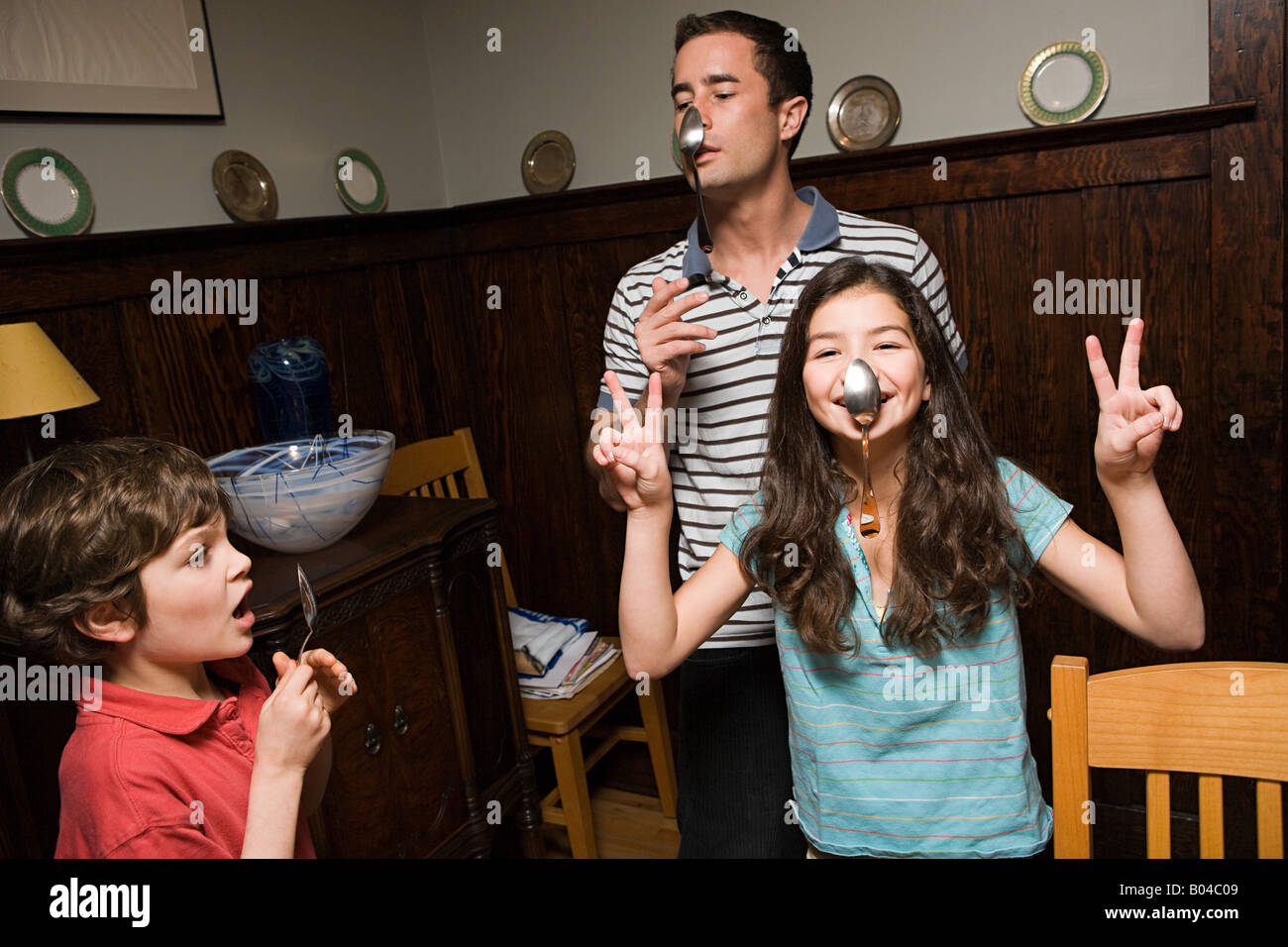 A father and his children hanging spoons on their noses - Stock Image