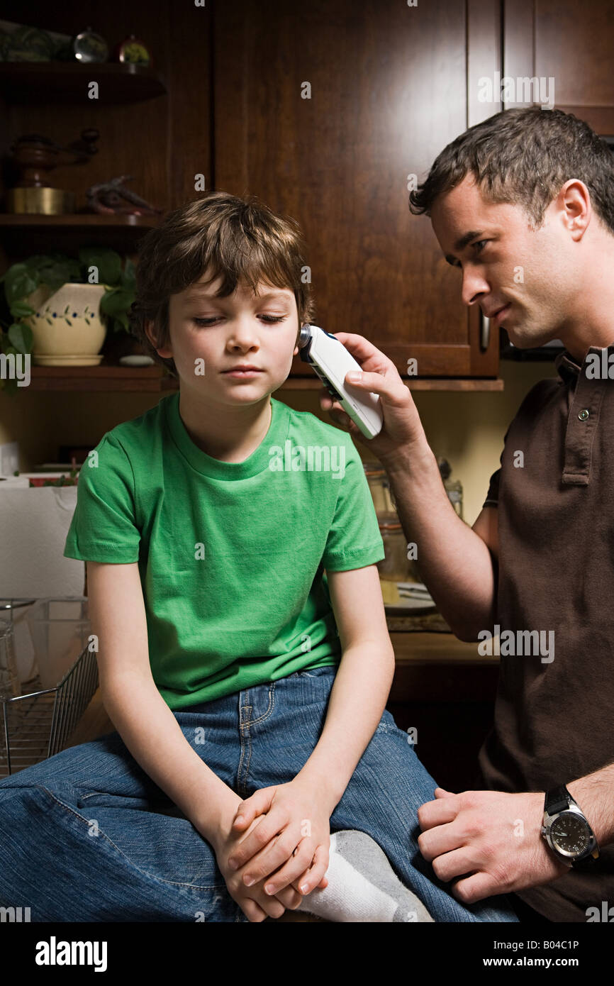 A father checking his sons temperature Stock Photo