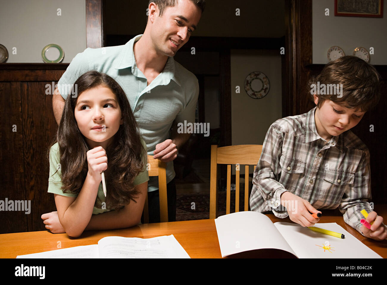 A father supervising his childrens homework Stock Photo