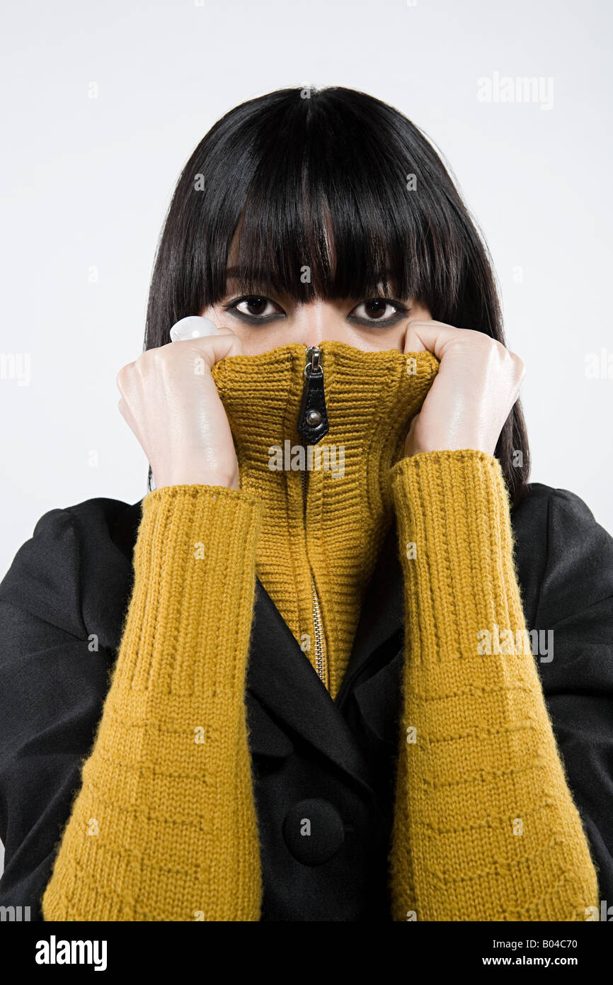 Japanes woman peering over sweater - Stock Image