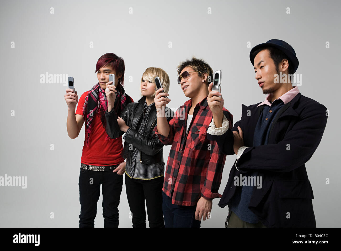 Four people using camera telephones - Stock Image