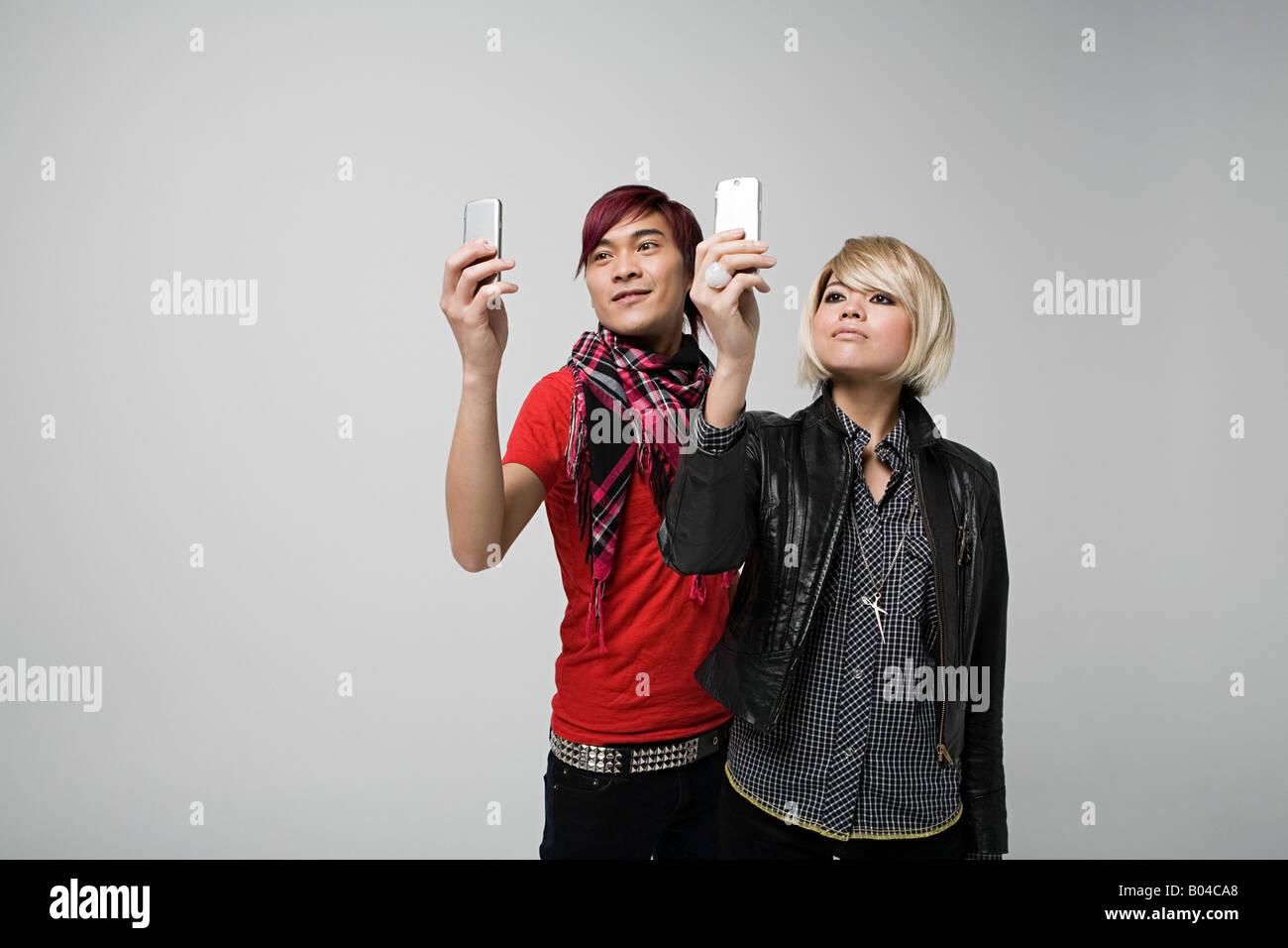 Couple using camera telephones - Stock Image