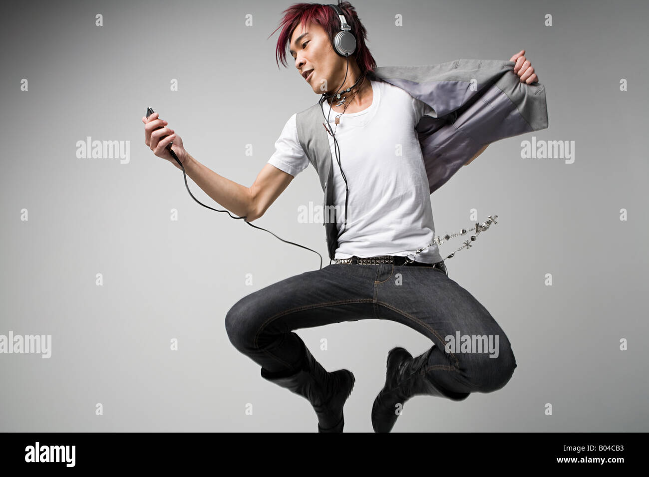 Japanese man listening to mp3 player - Stock Image