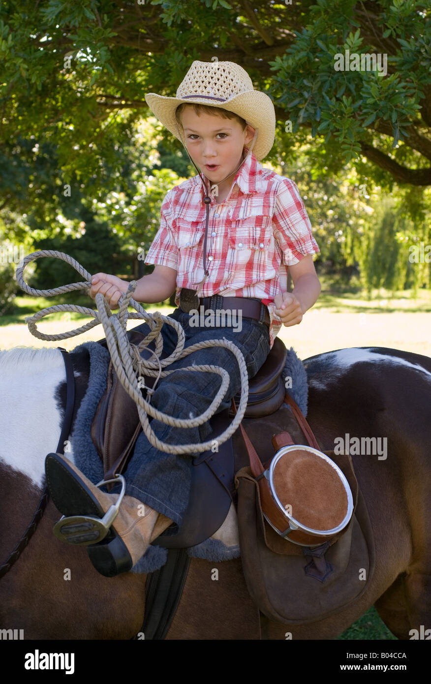 A boy riding a horse and holding a lasso - Stock Image