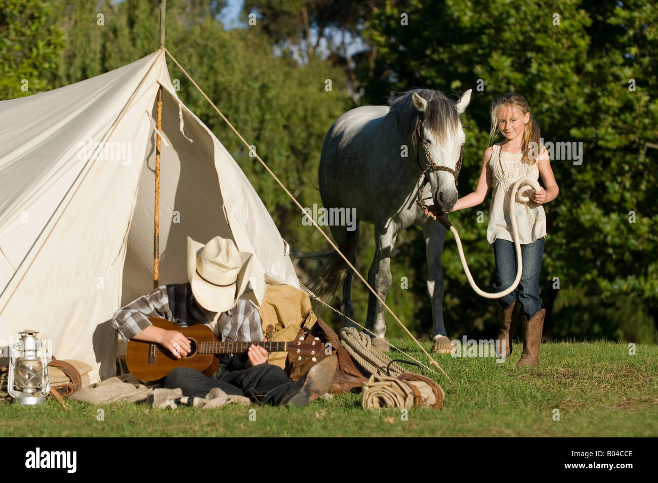 A boy playing a guitar and a girl walking a horse - Stock Image