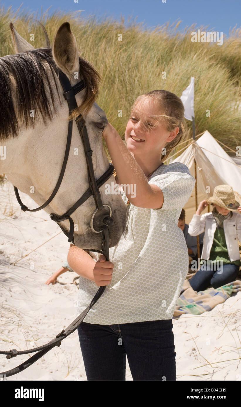 A girl stroking a horse - Stock Image