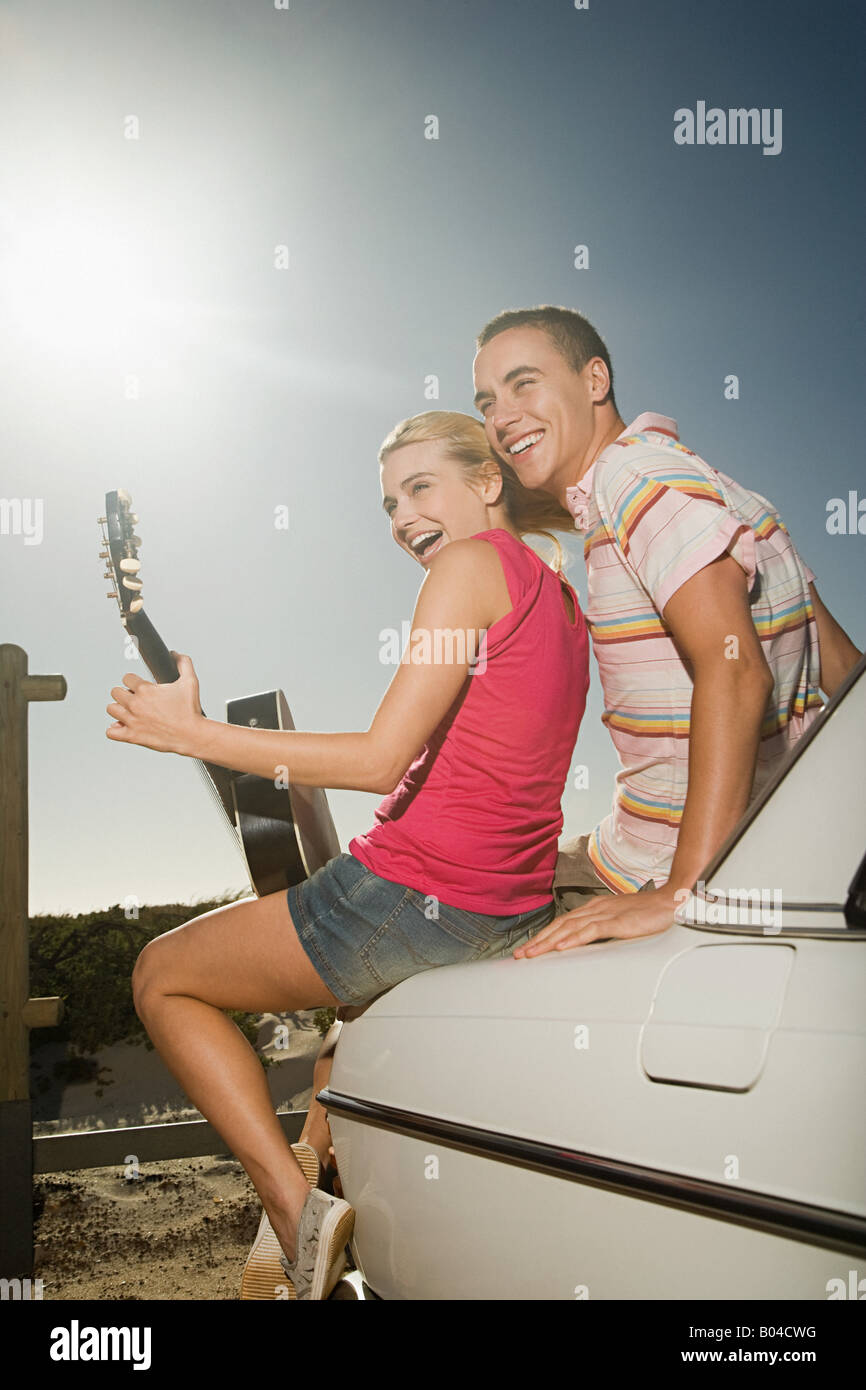 A young woman playing a guitar and a young man - Stock Image