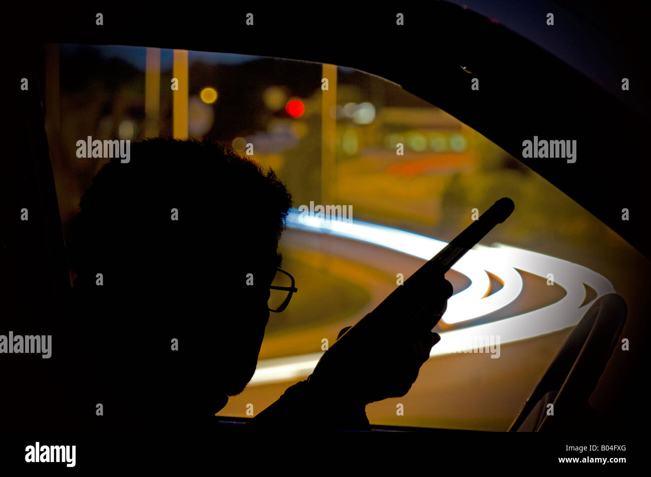 terrorist sniper with rifle parked over busy highway at night - Stock Image
