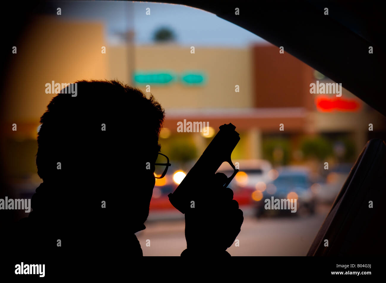 terrorist sniper with handgun parked at shopping mall at dusk - Stock Image