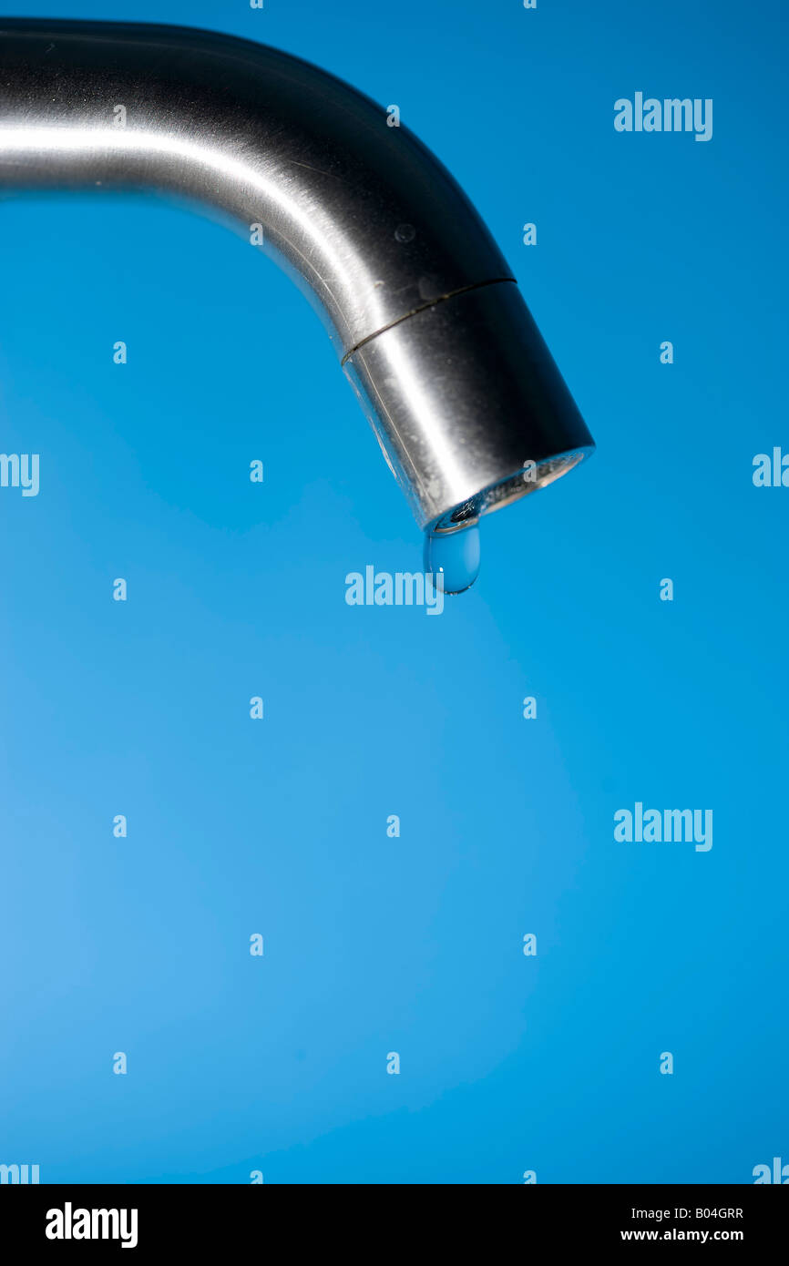 close-up of a water drop hanging from a faucet, blue background - Stock Image