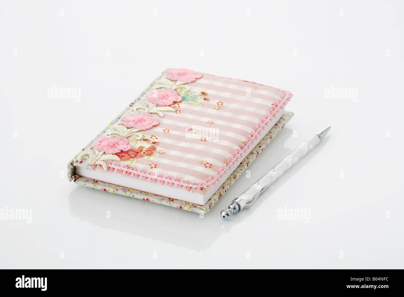 Pretty fabric covered journal on white background. - Stock Image