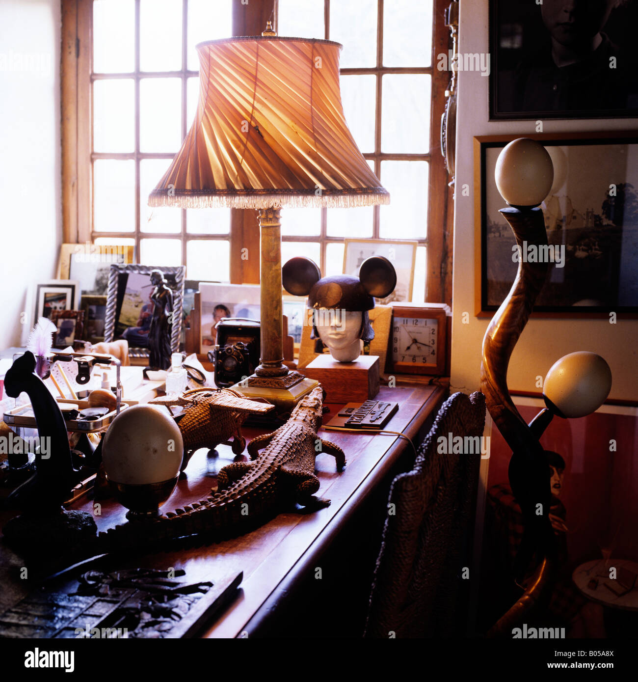 view of desk cluttered with eclectic collection of objects and family photographs - Stock Image
