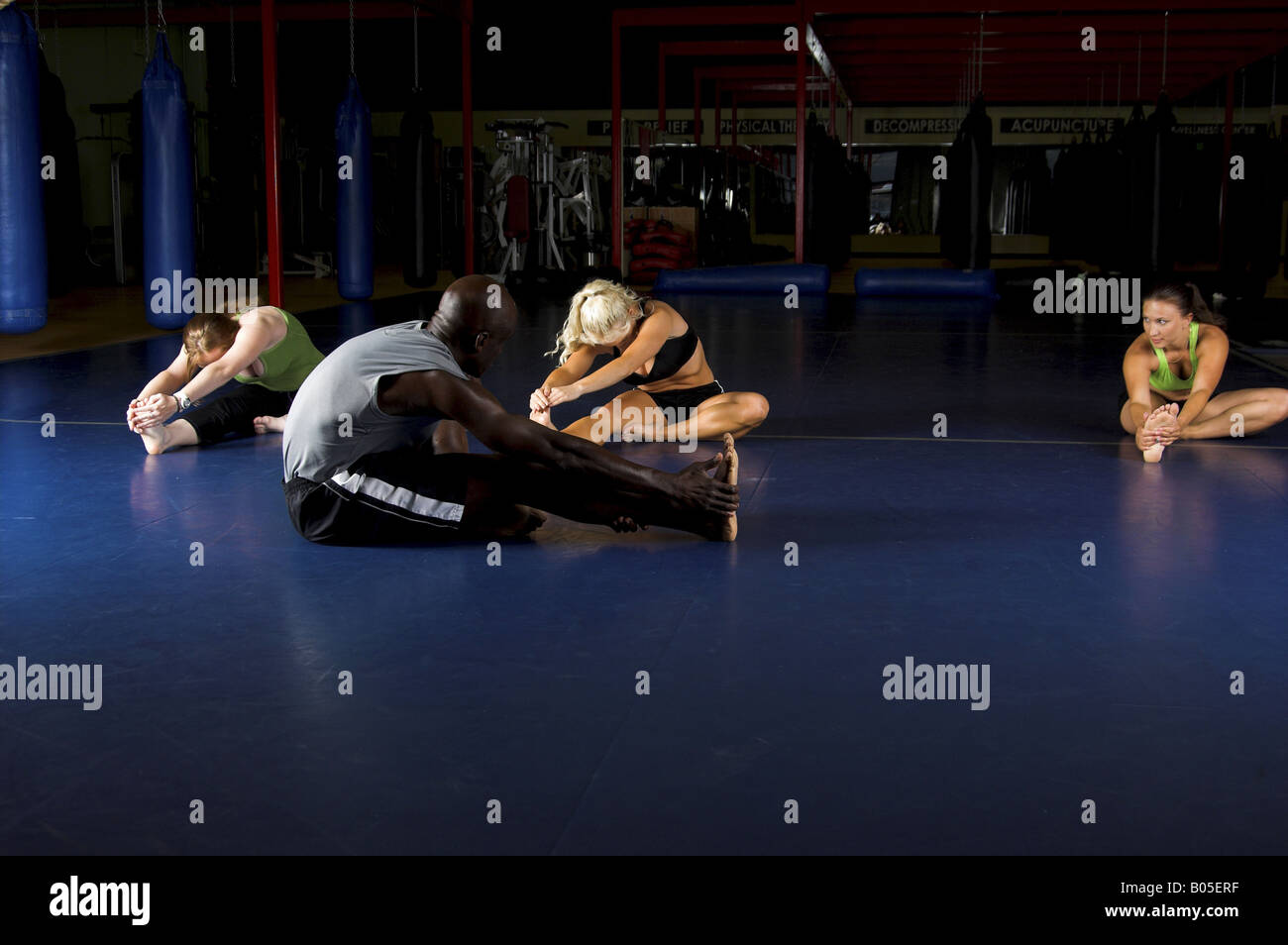women MMA team and trainer stretching out during a warm up