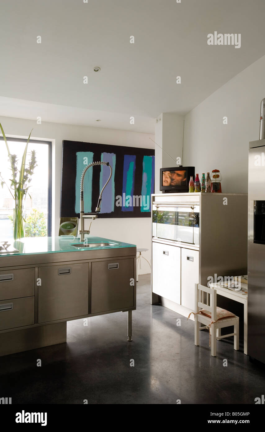 Stainless steel kitchen in converted 1950s factory - Stock Image