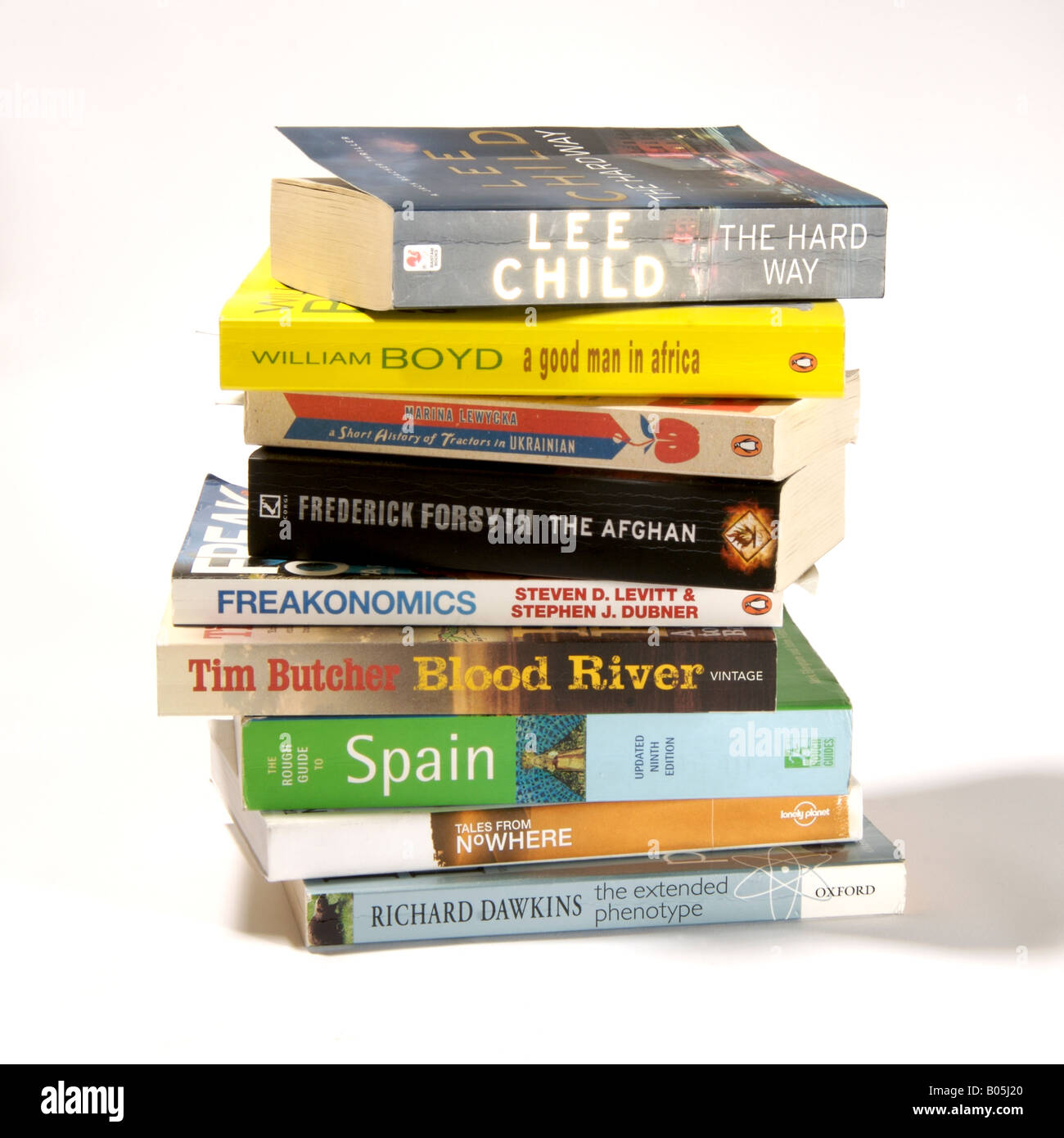 Pile of paperback on white background. Stack of bestselling novels, factual, fiction and travel books. - Stock Image